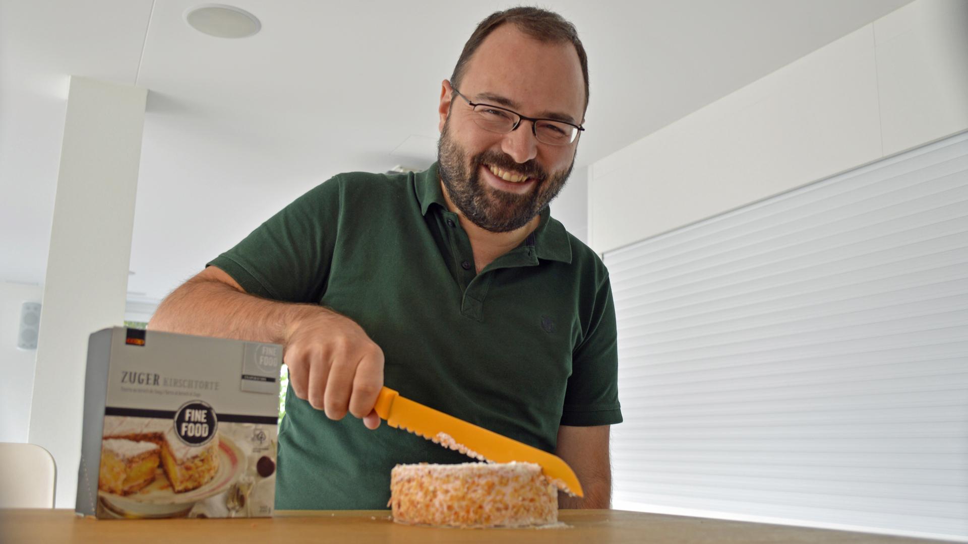 Stefan schneidet Zuger Kirschtorte an
